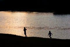 Duas crianças que jogam ao lado de um lago no por do sol Fotos de Stock Royalty Free