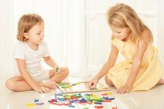 Duas crianças que jogam com o mosaico de madeira em sua sala Imagens de Stock