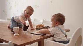 Duas crianças que jogam na cozinha com cutelaria em uma tabela coberta com a farinha vídeos de arquivo