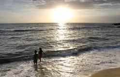 Duas crianças que jogam na linha costeira durante o por do sol Imagem de Stock