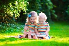 Duas crianças que leem no jardim do verão Foto de Stock Royalty Free