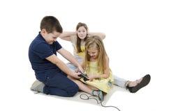 Duas crianças que lutam por jogos de vídeo A irmã idosa irritada que cobre suas orelhas com suas mãos não pode escutando Imagem de Stock Royalty Free