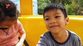 Duas crianças que montam em ferris amarelos rodam dentro o parque de diversões filme