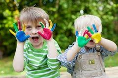 Duas crianças que mostram as mãos pintadas fora Fotos de Stock Royalty Free