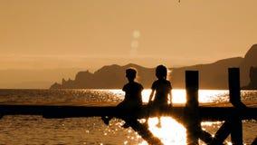 Duas crianças que sentam-se na ponte no por do sol video estoque