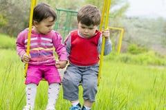 Duas crianças que têm o divertimento em um balanço no dia de verão Fotografia de Stock Royalty Free