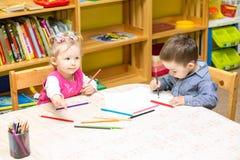 Duas crianças que tiram com os lápis coloridos no pré-escolar na tabela Desenho da menina e do menino Foto de Stock