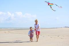 Duas crianças que voam o papagaio na praia foto de stock