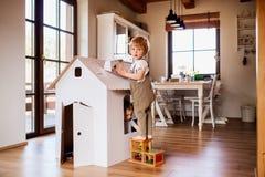 Duas crian?as da crian?a que jogam com uma casa do papel da caixa dentro em casa fotos de stock royalty free