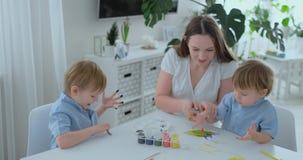 Duas crian?as dos meninos e da m?e s?o contratadas no desenvolvimento criativo que faz trabalhos de casa pelo manejo no papel E video estoque