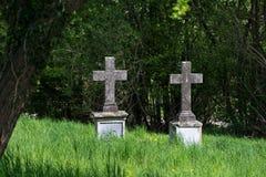 Duas cruzes de pedra velhas como lápides em um cemitério coberto de vegetação Fotografia de Stock