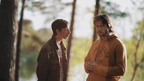 Duas discussões masculinas dos amigos no por do sol morno bonito iluminam-se na floresta video estoque