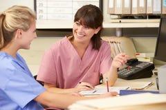 Duas enfermeiras que trabalham na estação das enfermeiras Fotos de Stock Royalty Free