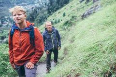 Duas escaladas dos turistas na montanha sob a chuva fotos de stock royalty free