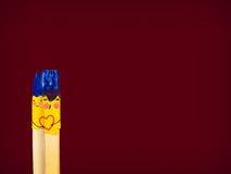 Duas escovas coloridas com sorriso guardam uma lareira e um beijo Foto de Stock
