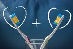Duas escovas de dentes em um fundo azul e em dois corações com o a mais o sinal fotografia de stock royalty free