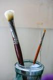 Duas escovas de pintura em um frasco de vidro imagens de stock