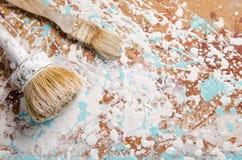 Duas escovas em um cartão duro manchado com pintura Imagens de Stock