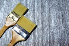 Duas escovas para o reparo em uma prata cinzenta pintaram o fundo Foto de Stock