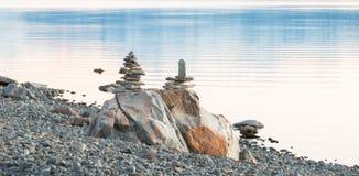 Duas esculturas de rochas de equilíbrio em um lago suportam Foto de Stock Royalty Free