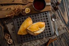 Duas especiarias dispersadas bolos de cravos-da-índia do limão da canela Passe a caneca de chá em um fundo escuro de madeira Na c fotos de stock