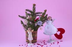 Duas estatuetas do anjo no fundo cor-de-rosa Fotografia de Stock
