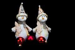 Duas estatuetas dos bonecos de neve com as quinquilharias vermelhas no preto Imagens de Stock Royalty Free