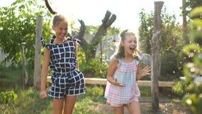 Duas estudantes bonitas estão saltando no jardim quando hosed com água Feriados de escola, resto no video estoque