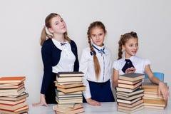Duas estudantes das meninas sentam-se com os livros em sua mesa na lição na escola imagens de stock royalty free