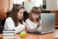 Duas estudantes executam a tarefa usando o caderno imagem de stock