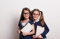 Duas estudantes pequenas com os vidros e o uniforme que estão em um estúdio, guardando blocos de notas Fotografia de Stock