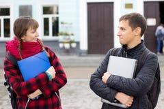 Duas estudantes universitário que falam e que flertam Fotos de Stock Royalty Free