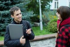 Duas estudantes universitário que falam e que flertam Imagens de Stock Royalty Free