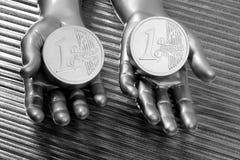 Duas euro- moedas de prata nas mãos futuristas do robô Imagens de Stock