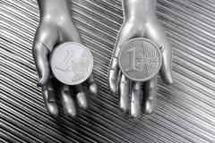 Duas euro- moedas de prata nas mãos futuristas do robô Fotos de Stock