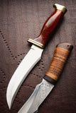 Duas facas de caça no fundo marrom fotografia de stock