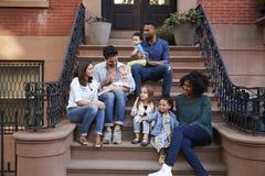 Duas famílias com as crianças que sentam-se em corcundas dianteiras foto de stock