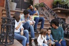 Duas famílias com as crianças que sentam-se em corcundas dianteiras fotos de stock