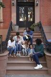 Duas famílias com as crianças que sentam-se nas corcundas dianteiras, verticais fotos de stock royalty free