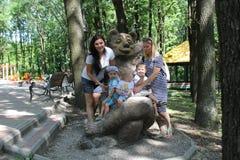 Duas famílias com três crianças Mães e crianças dos irmãos que têm o divertimento fora no jardim fotografia de stock