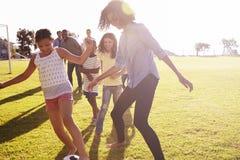 Duas famílias em um parque que joga o futebol foto de stock