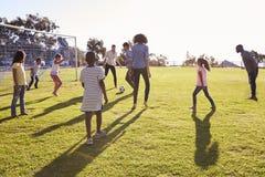 Duas famílias novas que jogam o futebol com suas crianças imagens de stock