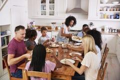 Duas famílias que apreciam comendo a refeição em casa junto foto de stock