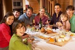 Duas famílias que apreciam a refeição no chalé alpino fotos de stock