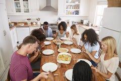 Duas famílias que dizem Grace Before Eating Meal Together imagens de stock royalty free