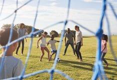 Duas famílias que jogam o futebol no parque visto através da rede do objetivo foto de stock