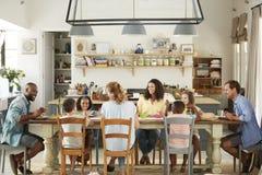 Duas famílias que têm o almoço junto na cozinha em casa foto de stock royalty free