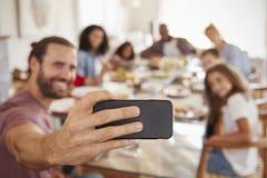 Duas famílias que tomam Selfie como apreciam a refeição em casa junto fotos de stock