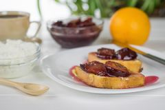 Duas fatias de pão francês brindado manchado com o doce da ameixa em uma placa branca Fotografia de Stock Royalty Free