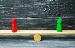 Duas figuras de madeira estão nas escalas de justiça rivais Conceito do negócio do benefício mútuo e sucesso dos sócios comerciai fotos de stock royalty free